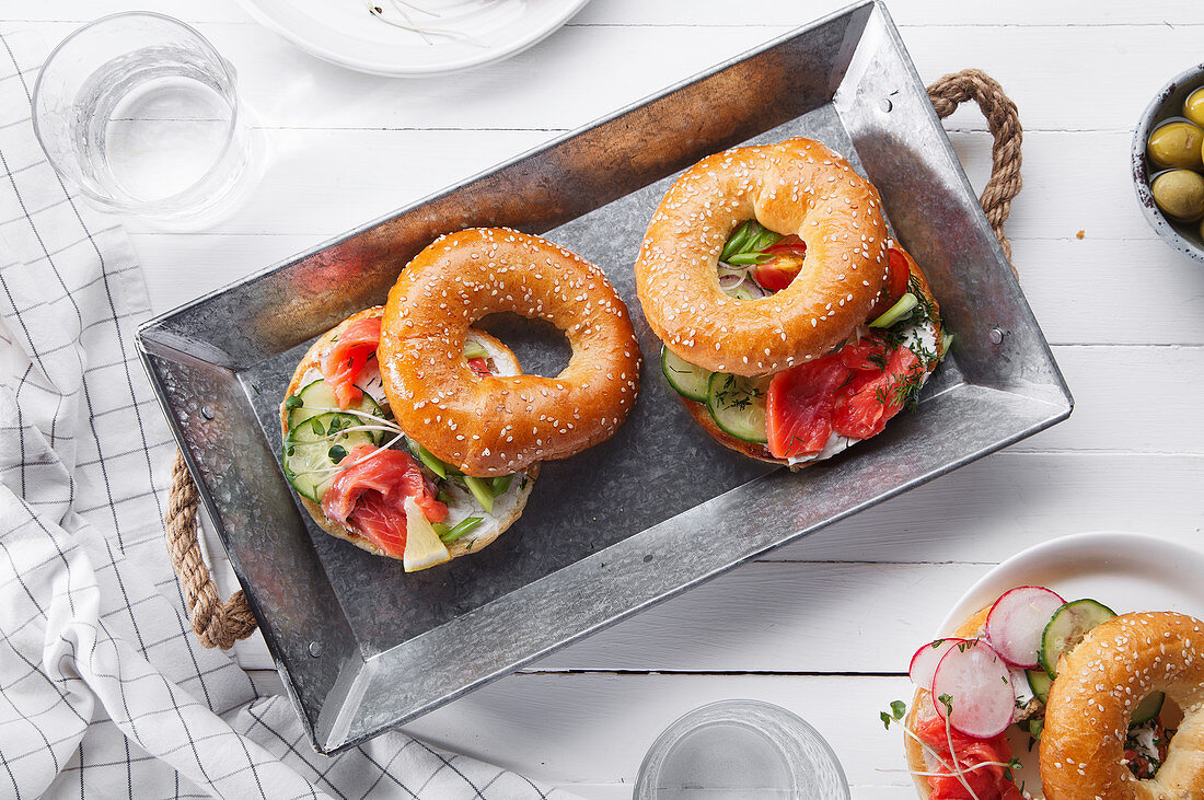 Bagels with salmon fish, cream cheese, cucumber and fresh radish slices on metallic tray