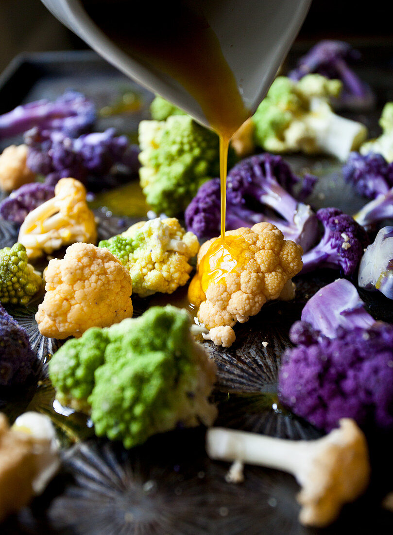 White cauliflower, purple cauliflower and romanesco broccoli florets being drizzled with turmeric oil