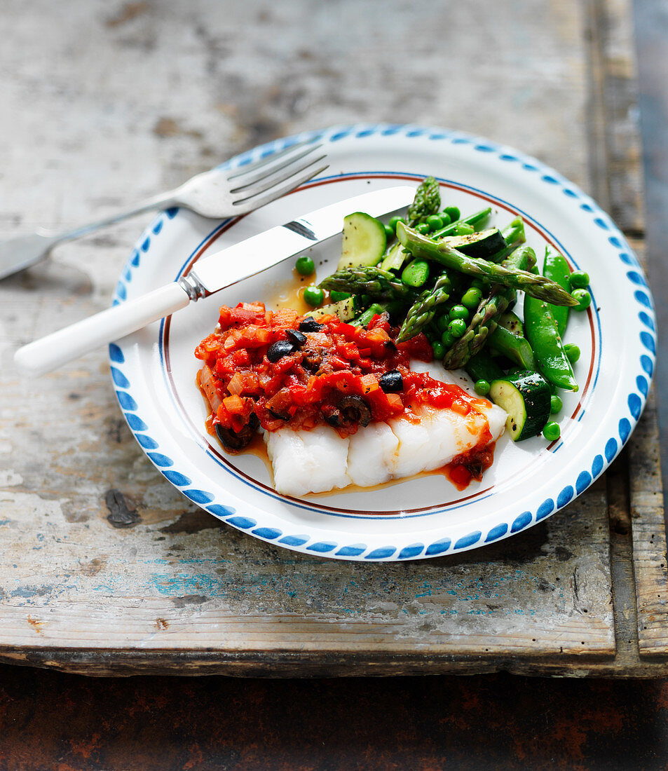 Fish fillet with tomato and olive sauce, asparagus, zucchini, and peas