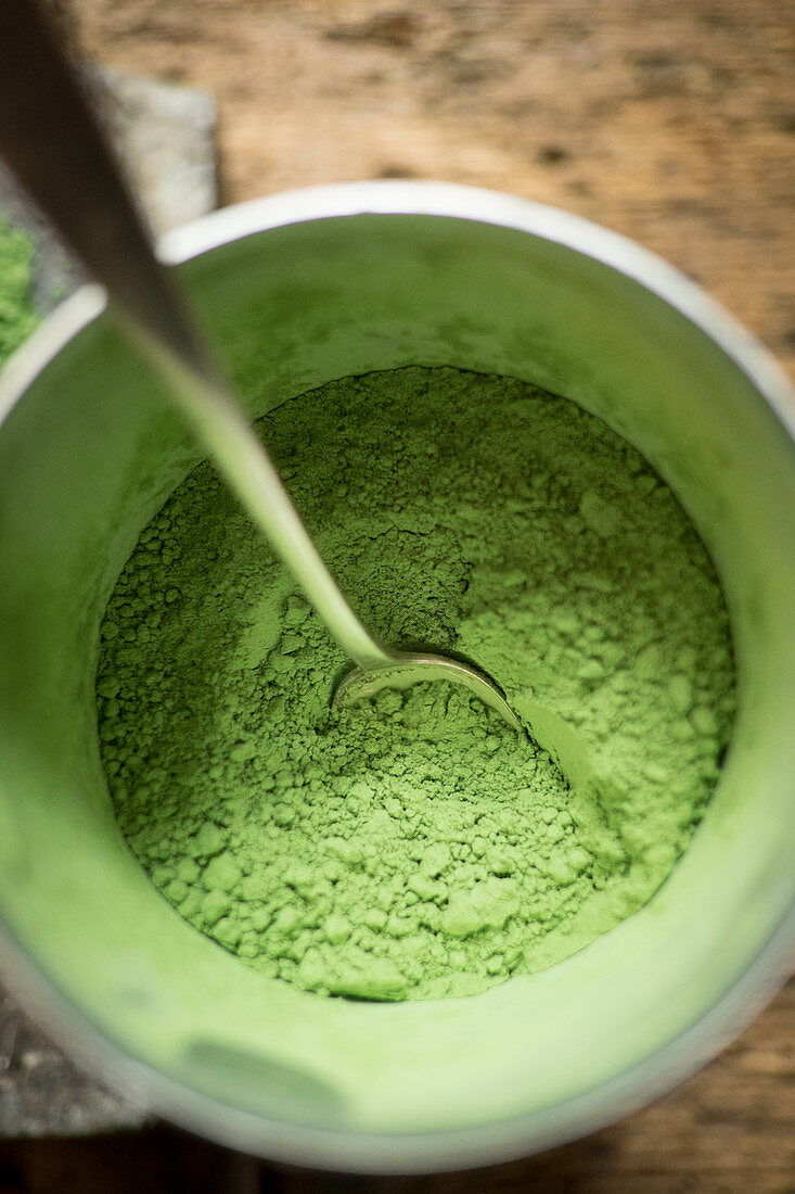 Wheatgrass powder in a glass with a spoon