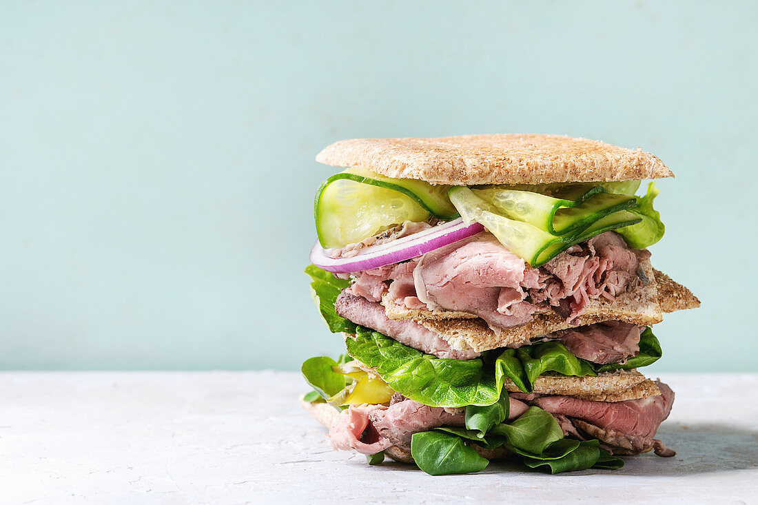 Beef and vegetables sandwiches with sliced meat, cucumber, green salad, rye whole grain bread in stack