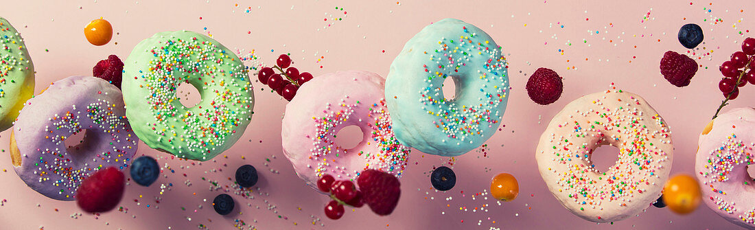 Sweet and colourful doughnuts with sprinkles and berries falling or flying in motion against pink pastel background