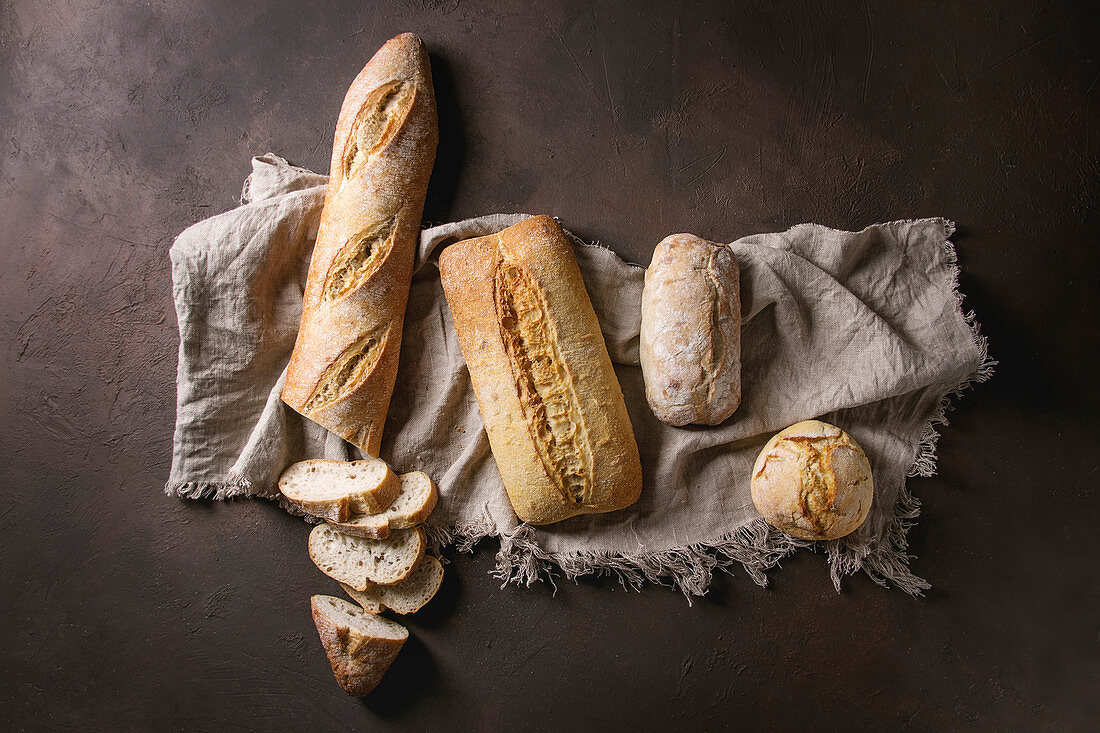 Variety of loafs fresh baked artisan white and whole grain bread on linen cloth over dark brown texture background