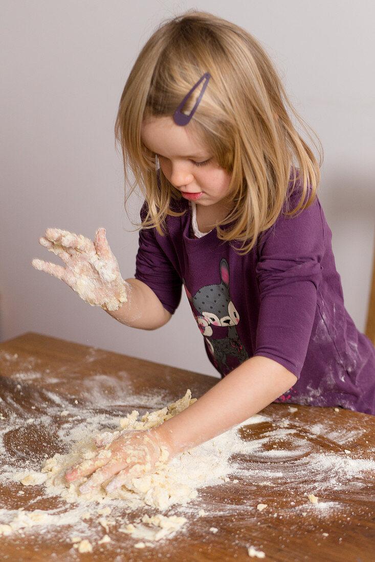 A little girl kneading dough