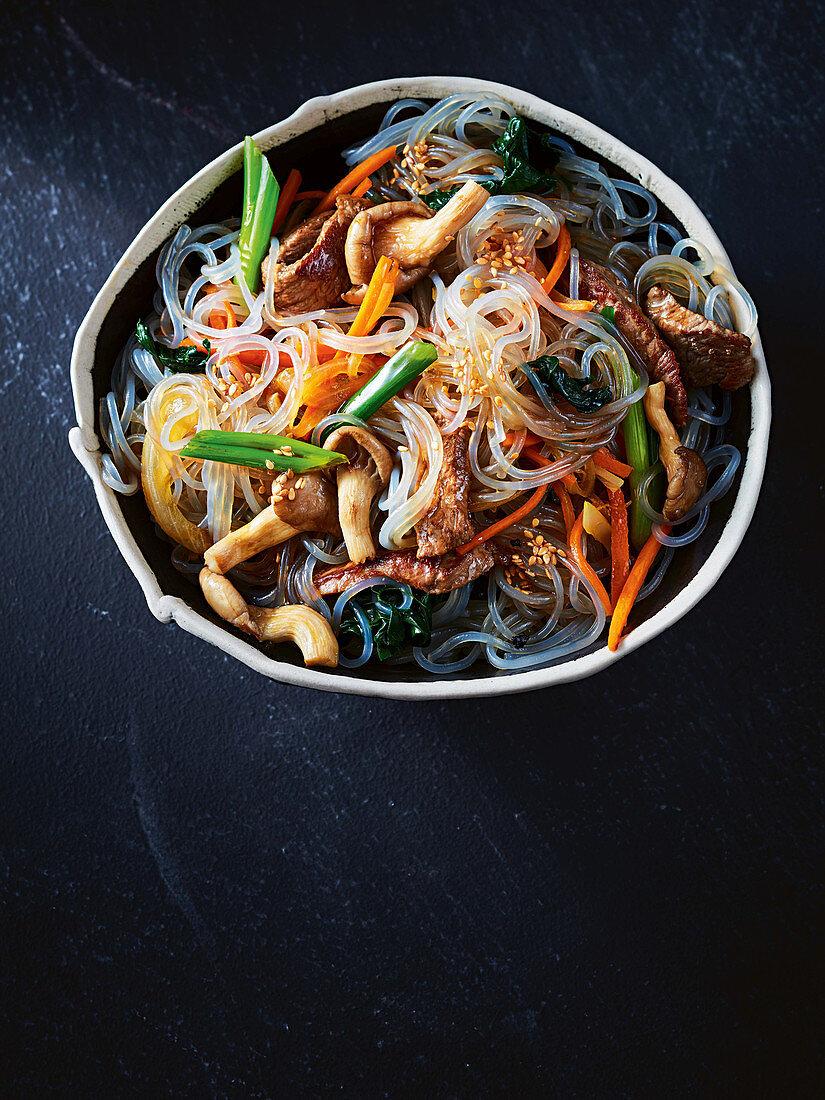 Japchae (Glasnudelgericht, Korea) mit Gemüse, Pilzen und Steakstreifen