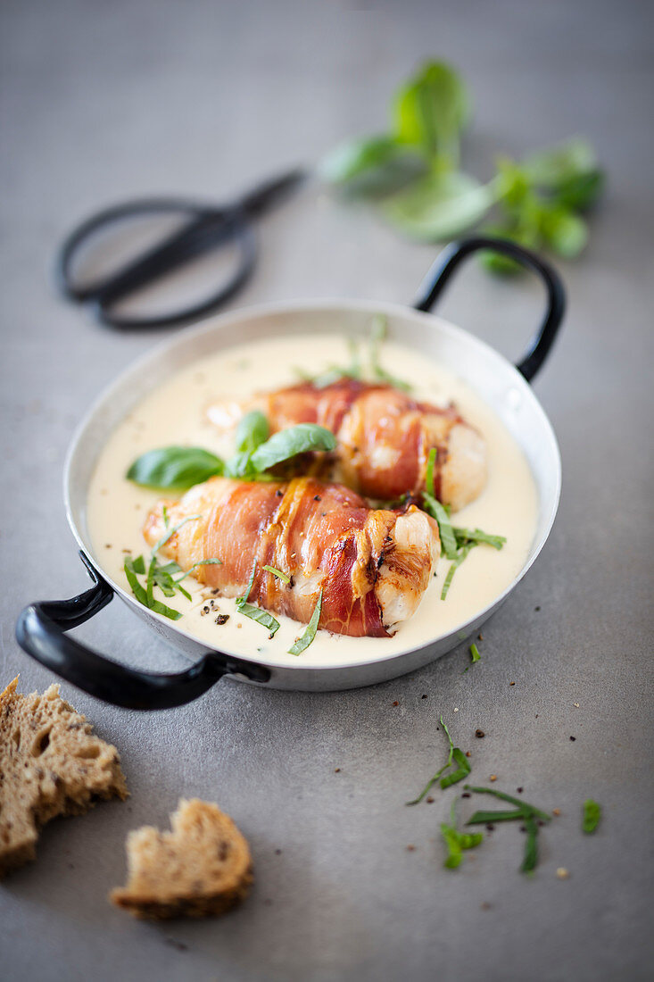 Chicken breast wrapped in bacon in a cream sauce in a pan