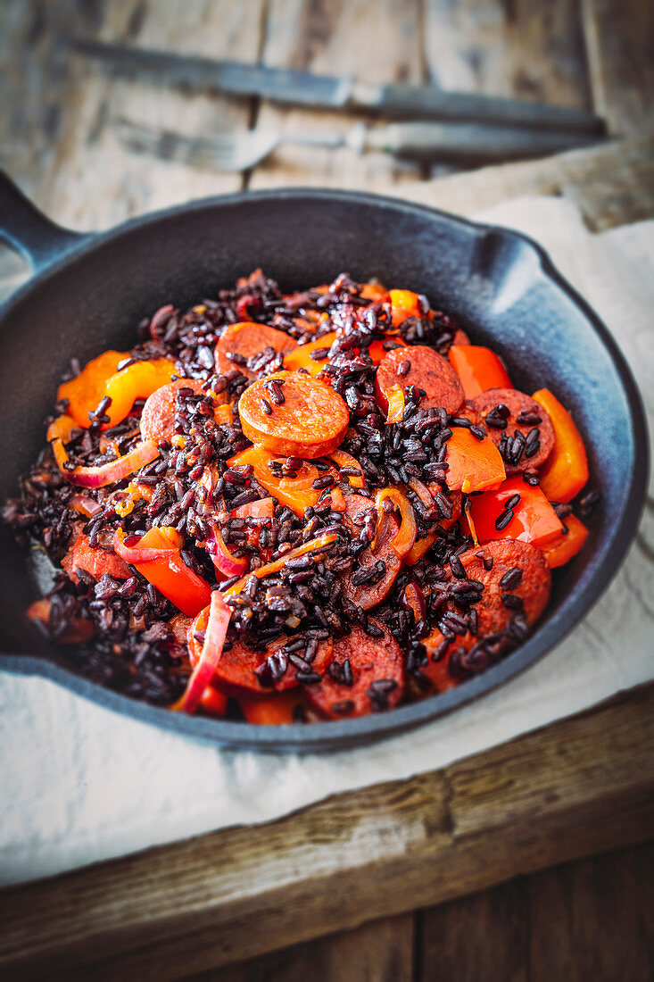 Red pepper and sausage with black rice in a cast iron pan