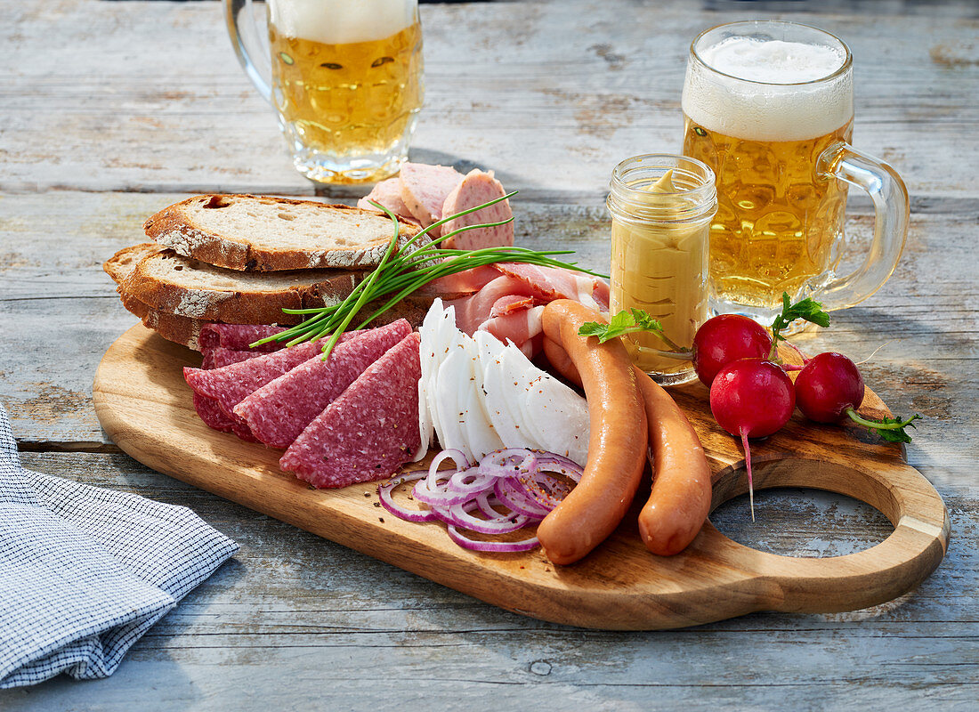 A snack board with sausages, mustard and bread served with bread