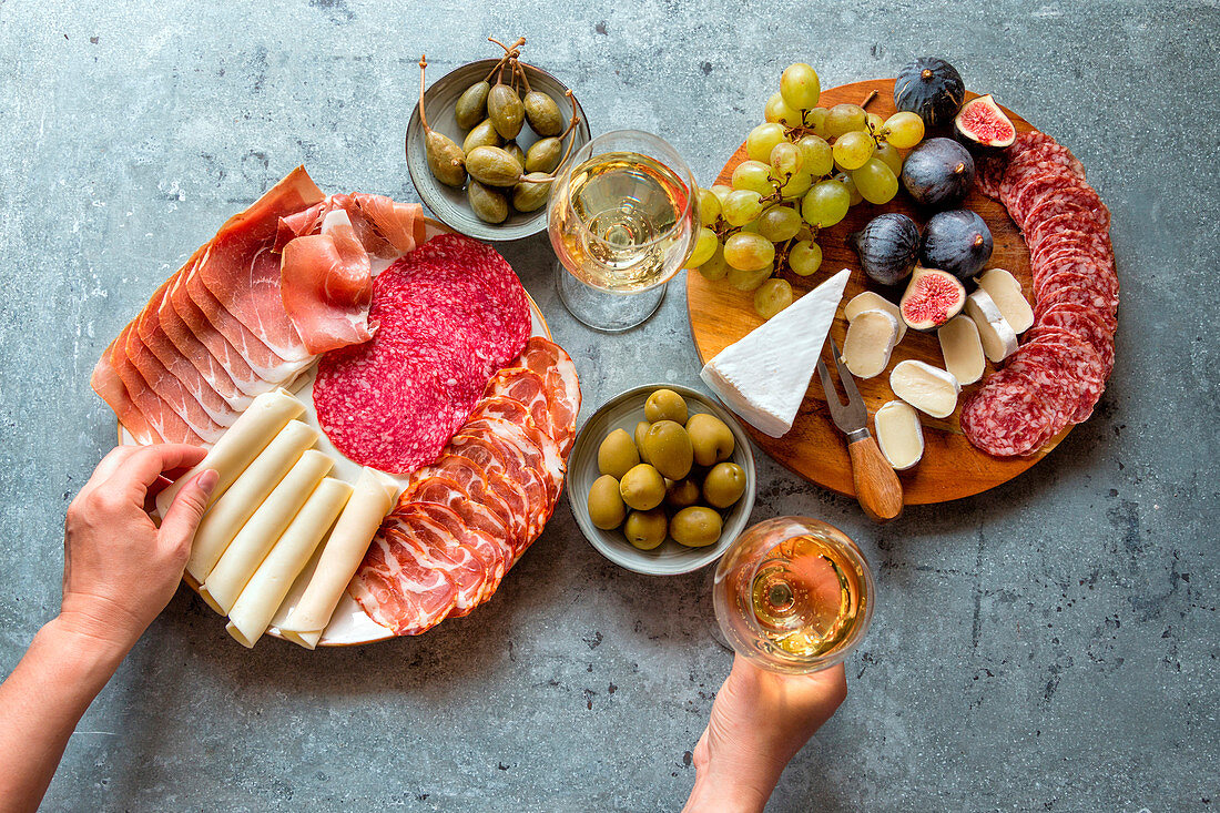 Antipasti platter and two glasses of white wine on the table