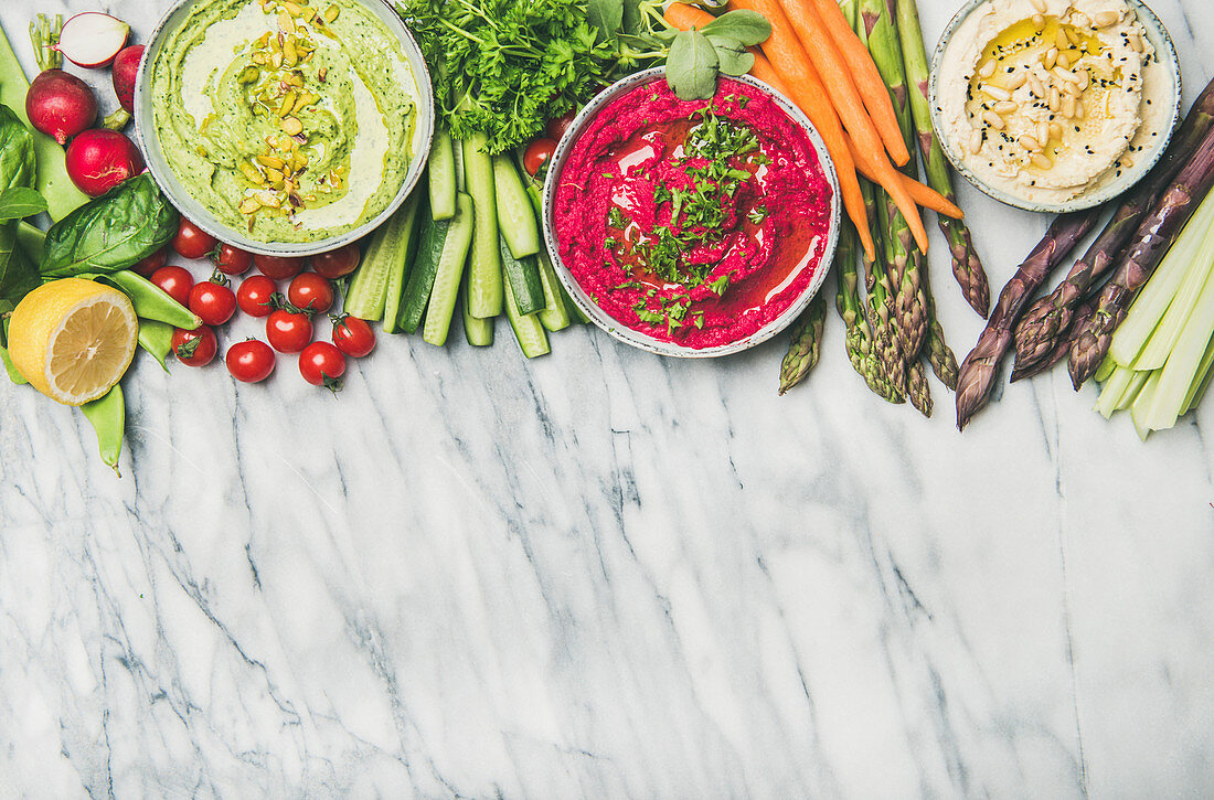 Chickpea, beetroot, spinach hummus dips with vegetables on marble background