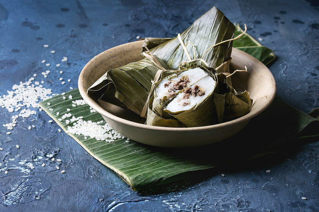 Asian rice piramidal steamed dumplings from rice tapioca flour with meat filling in banana leaves served in ceramic bowlwith rice above over blue texture background