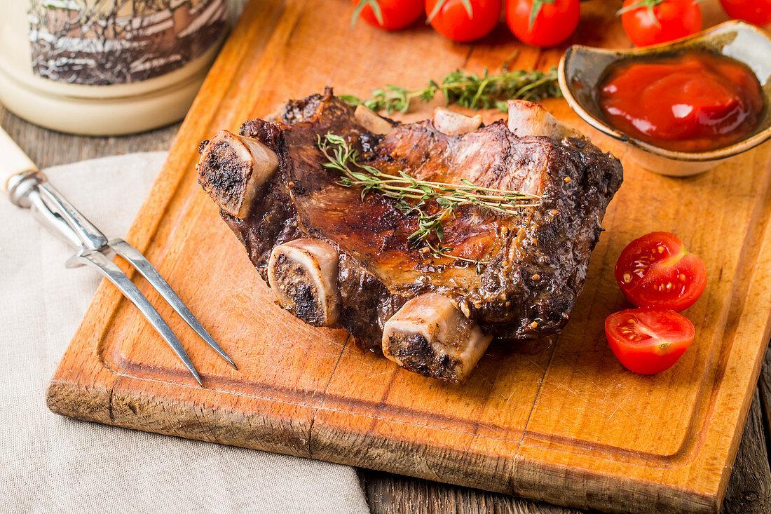 Gegrillte Rinderrippen mit Tomaten und Ketchup auf altem Holzbrett