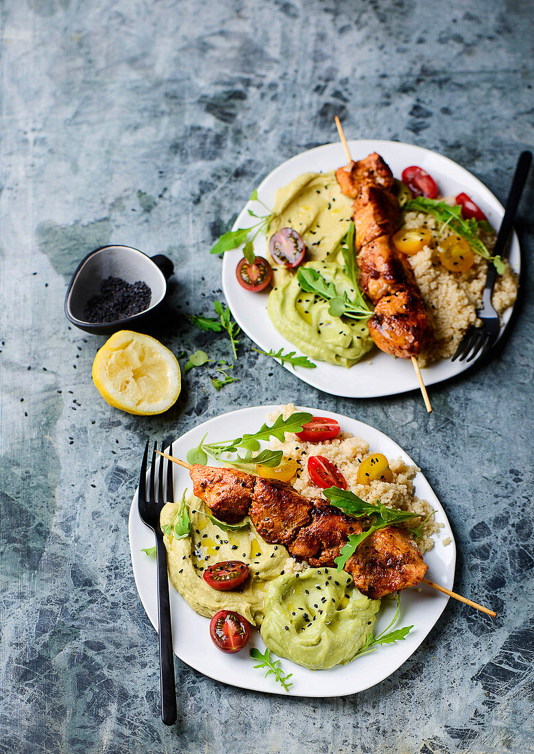 Chicken skewers with couscous, hummus and avocado purée