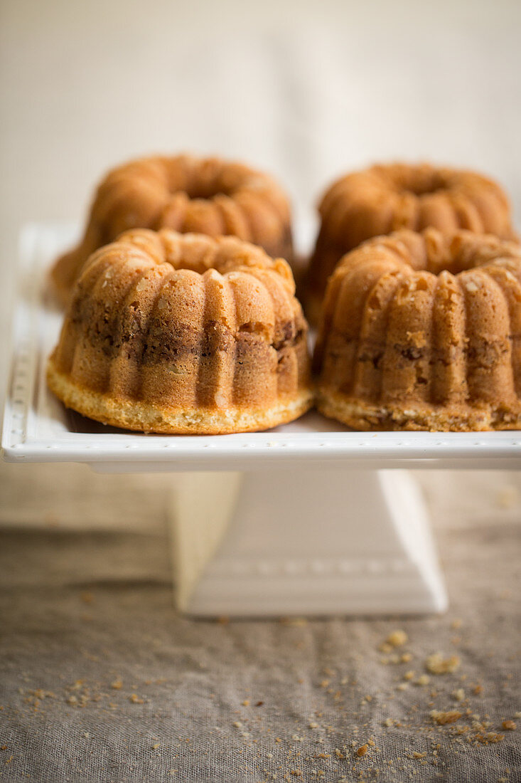 Four mini coffee cakes with almonds on a cake stand