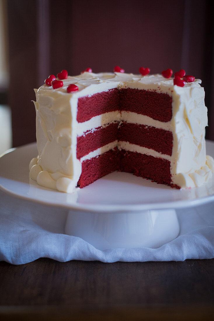 Red velvet cake on a cake stand, sliced