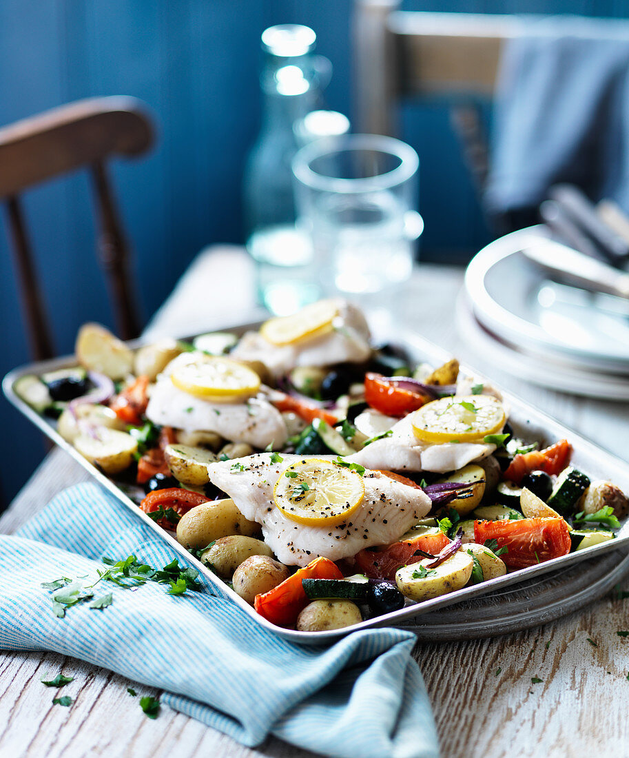 Baked fish with potatoes, vegetables and lemon