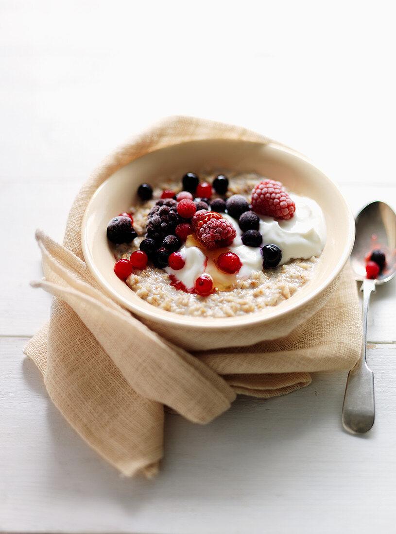 Porridge with mixed berries, cream and honey