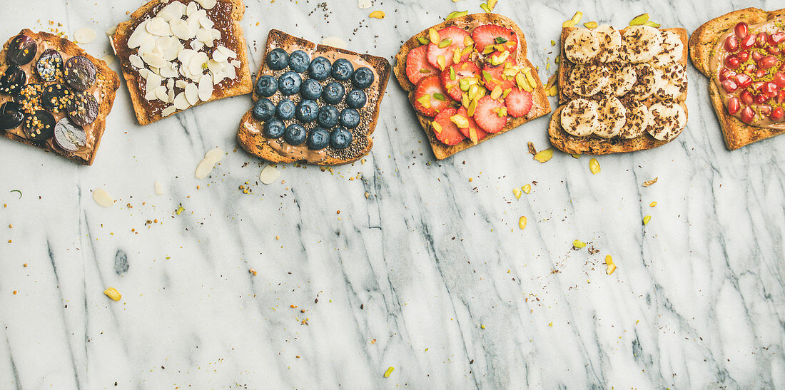Vegan whole grain toasts with fruit, seeds, nuts and peanut butter over marble background