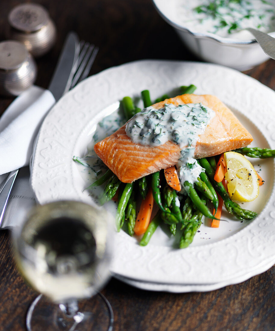 Salmon with parsley sauce, asparagus, green beans, carrots and lemon