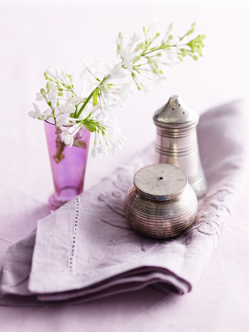 Silver salt and pepper shakers, flowers and a napkin