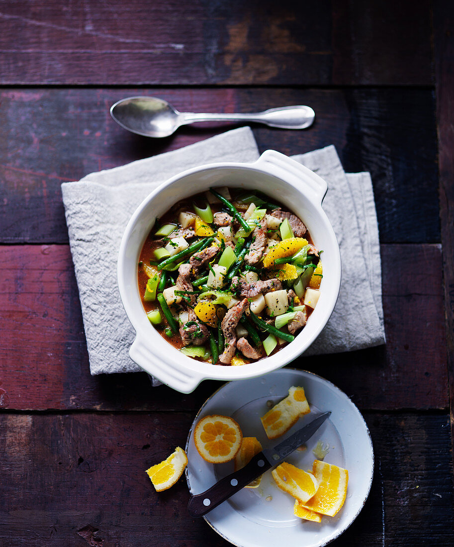 A stew made of pork, green beans, leeks, celery and oranges