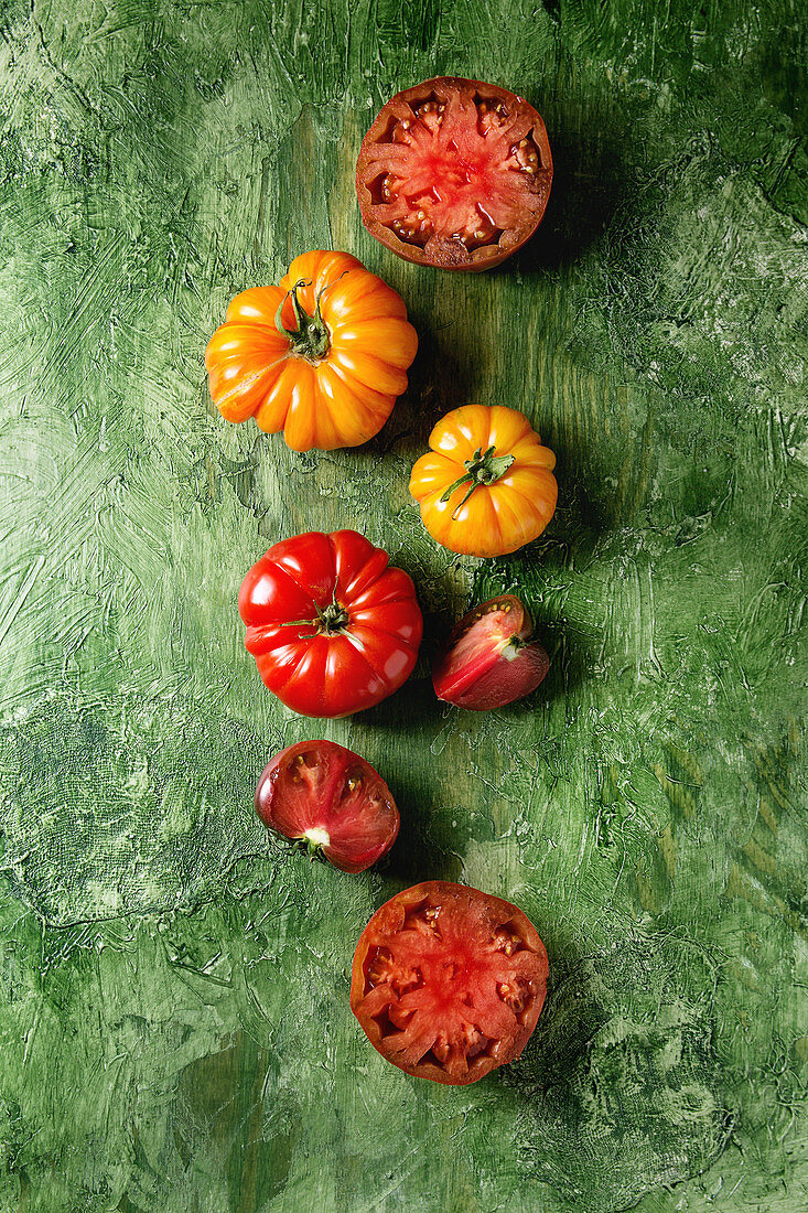 Variety of red and yellow organic tomatoes for salad over green texture background