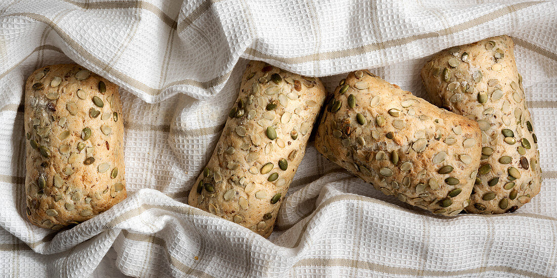 Four wholegrain pumpkin seed bread rolls on a brown and white tea towel