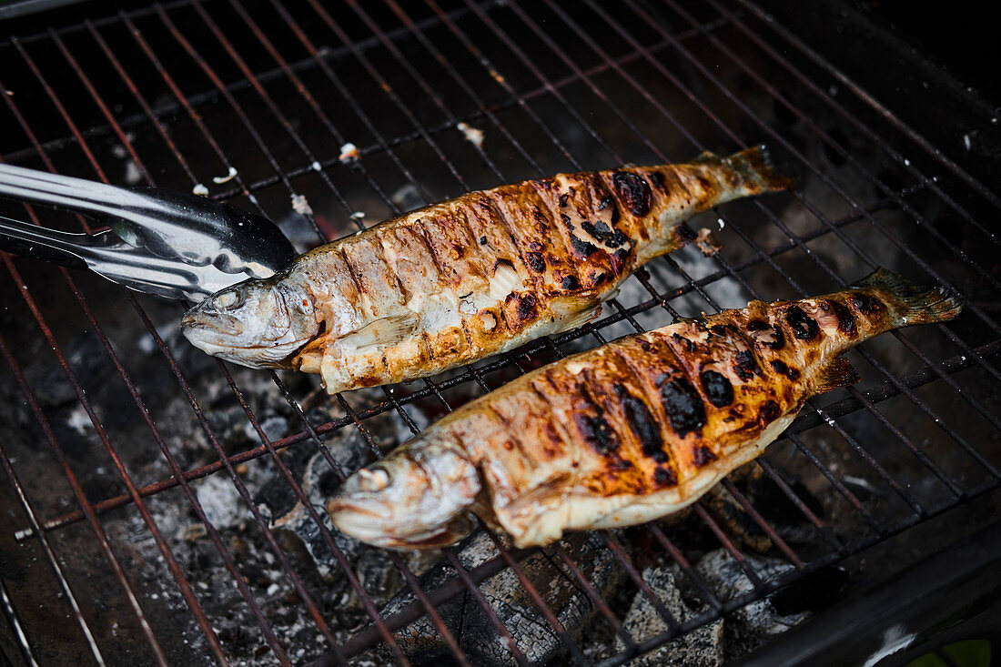 Top down view of man grilling fish and shrimps on skewers on barbecue with a tray of raw vegetables on the side