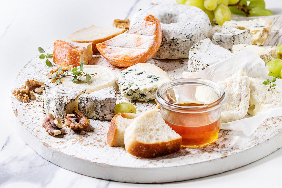 Cheese plate assortment of french cheese served with honey, walnuts, bread and grapes on white wooden