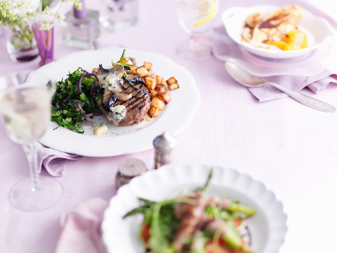 A beef steak with mushrooms, garlic butter, salad, vegetables and potatoes
