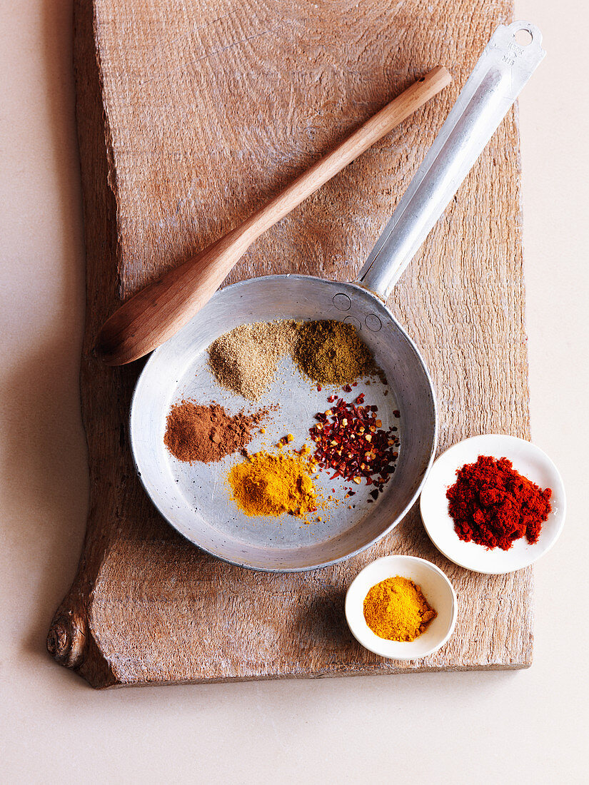 Various spices for a tagine dish: chili flakes, cumin, chilli powder and ginger