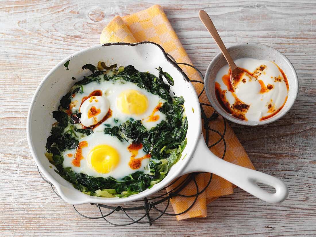Spinach with fried eggs in a pan with chilli yoghurt (low carb)