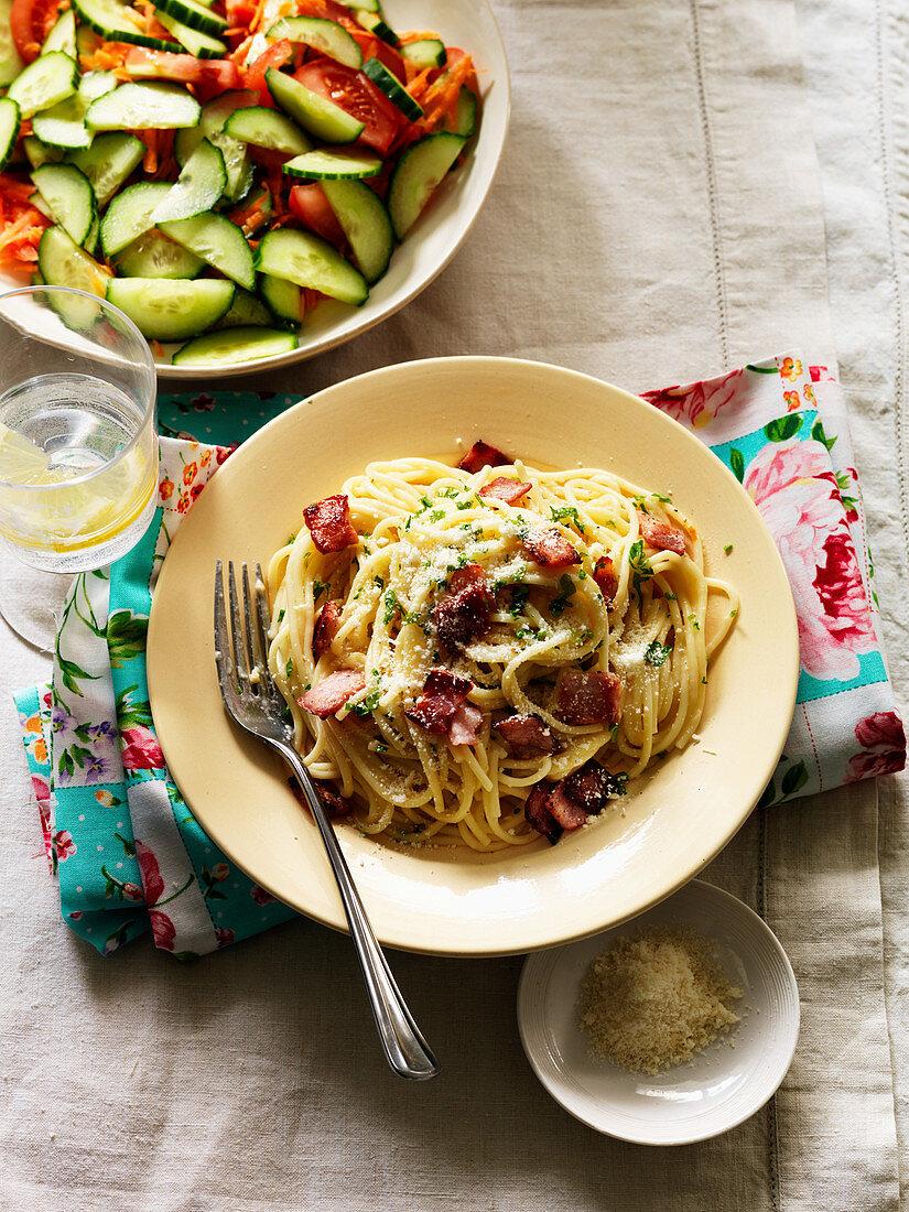 Spaghetti carbonara with tomato and cucumber salad