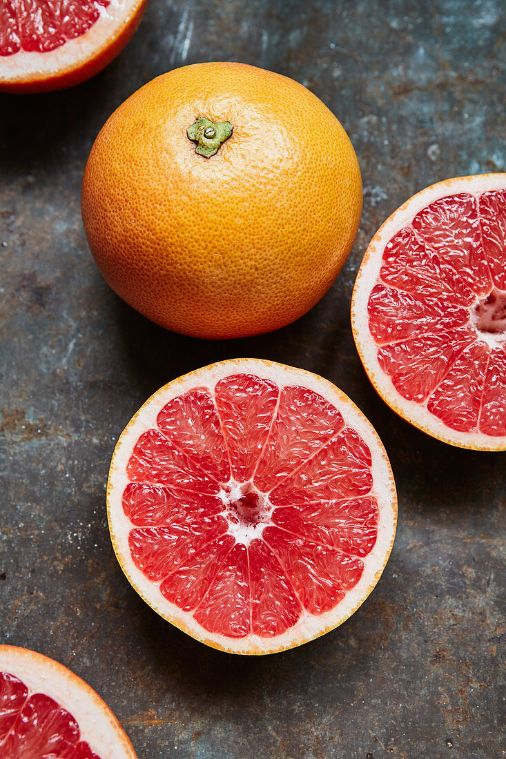 Pink grapefruits, whole and halved