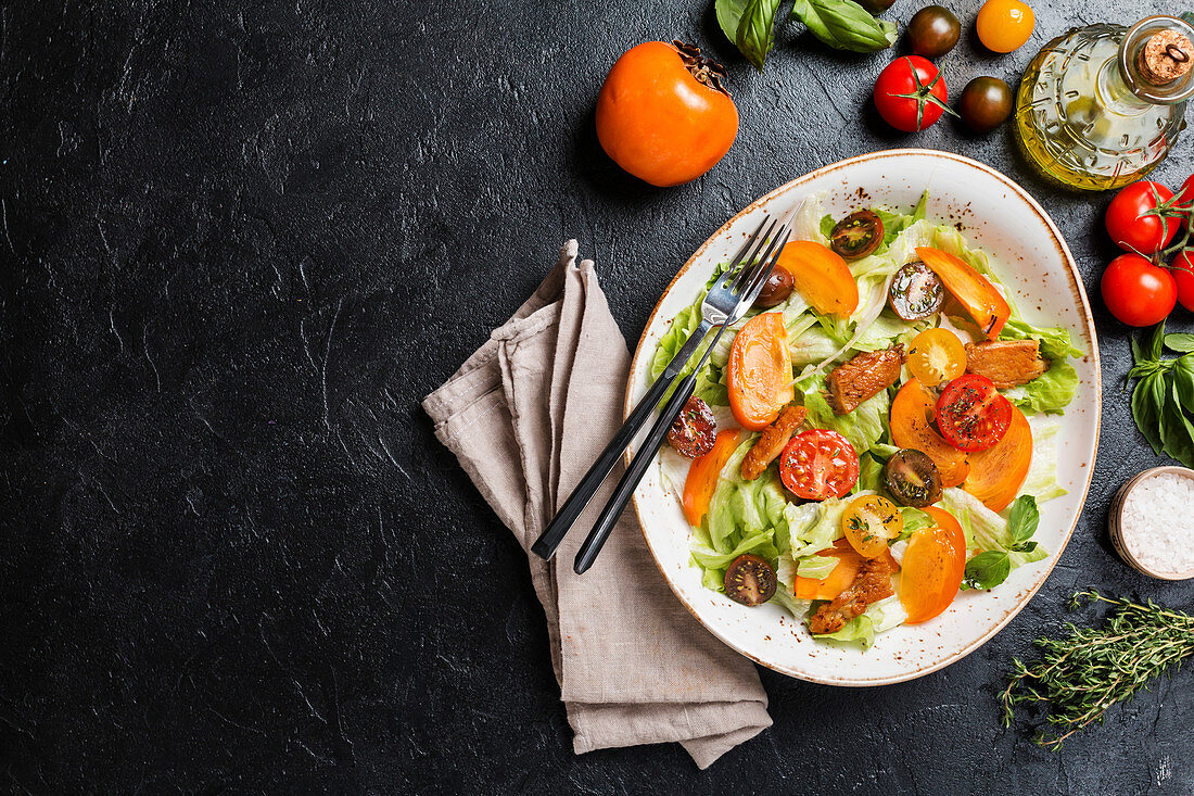 Fresh salad with persimmon, chicken and greens on black background, top view