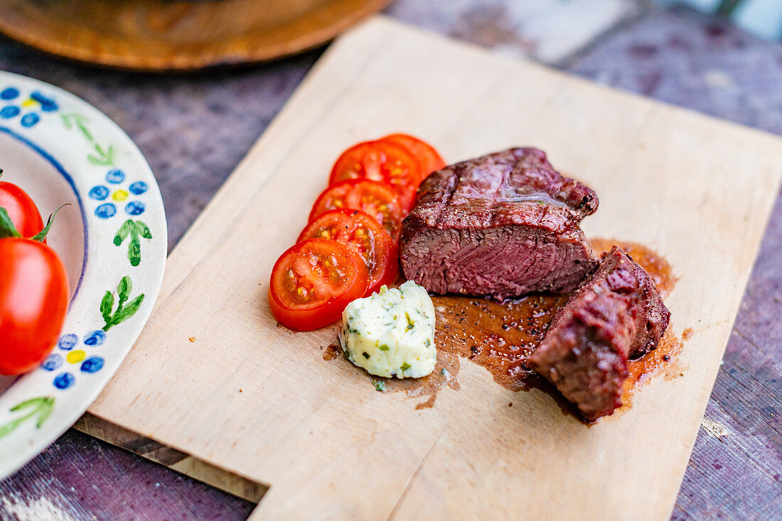Raw beef loin steaks with tomatoes and herb butter on a wooden board