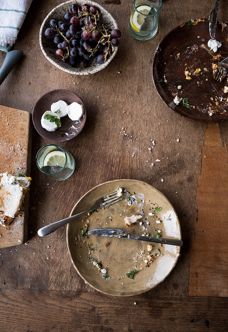 A wodden table with leftovers and goat cheese and grapes