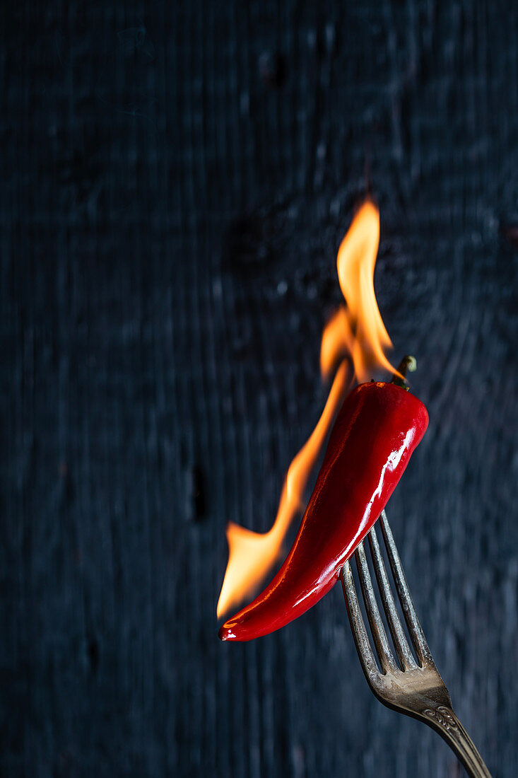 A burning chili pepper on a fork