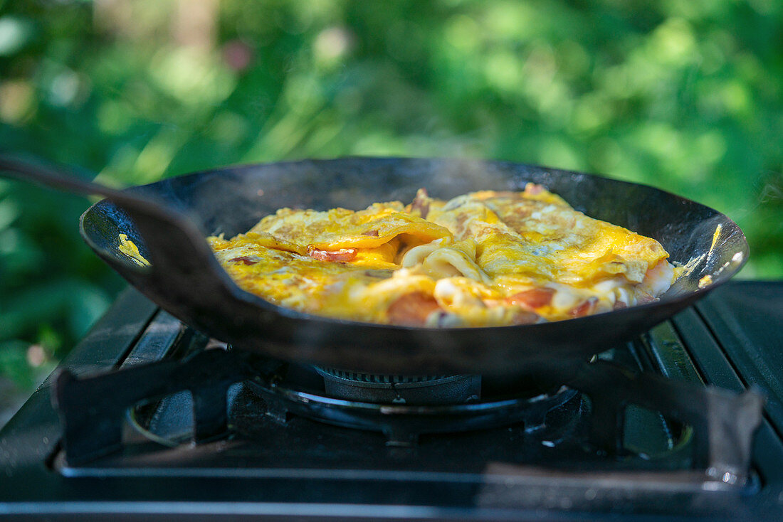 Scrambled eggs with bacon cooking outdoors