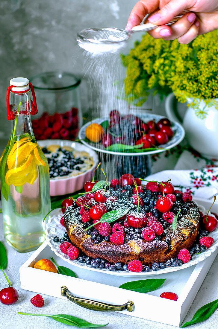 Sommerliche Obsttorte mit Beeren, Aprikosen, Kirschen und Puderzucker
