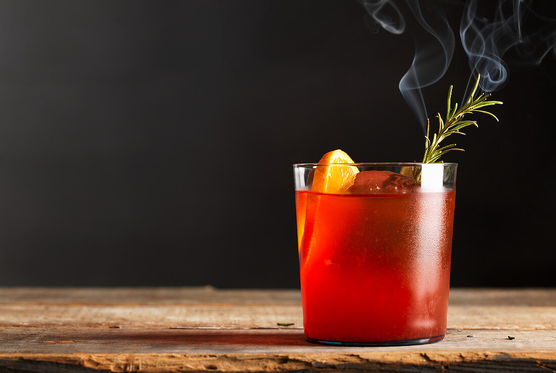 Red fruit cocktail with burnt rosemary and citrus
