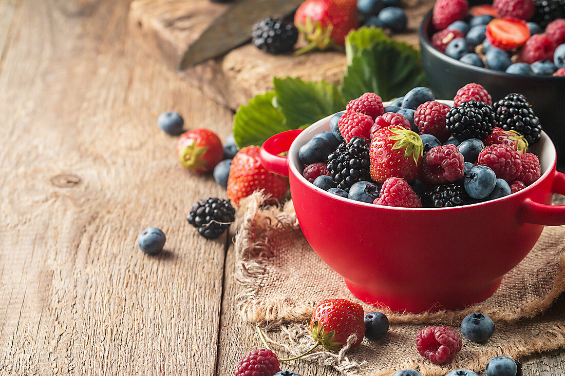 Ripe sweet different berries in red bowl