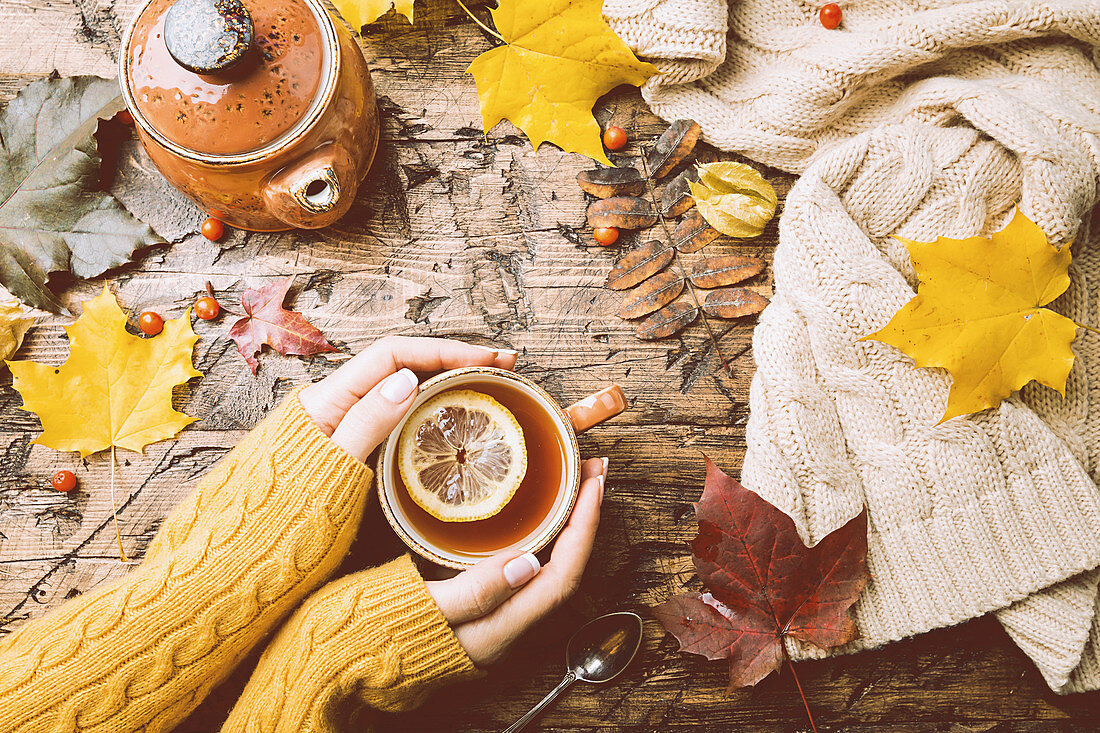 Cup of hot tea with lemon in woman's hands holding it over wooden autumn background