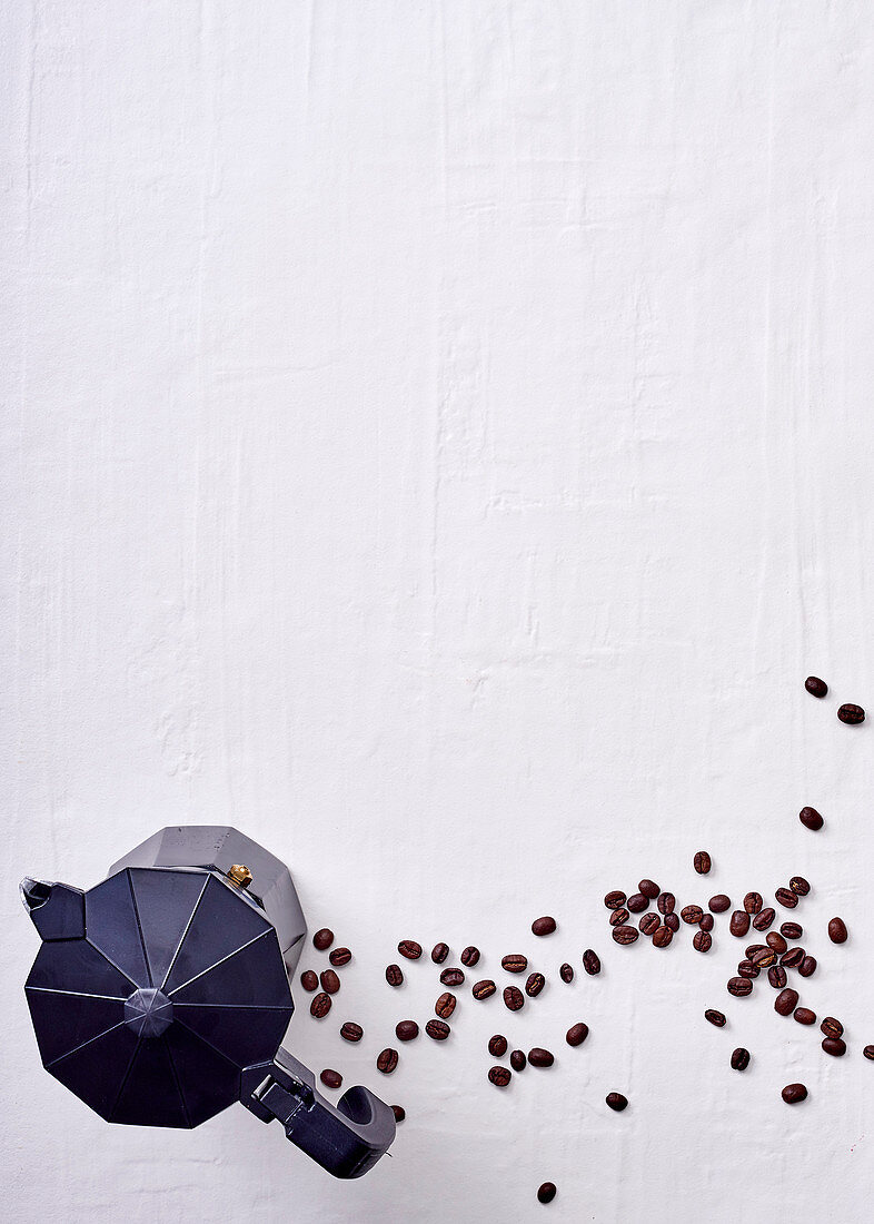 An espresso jug and coffee beans