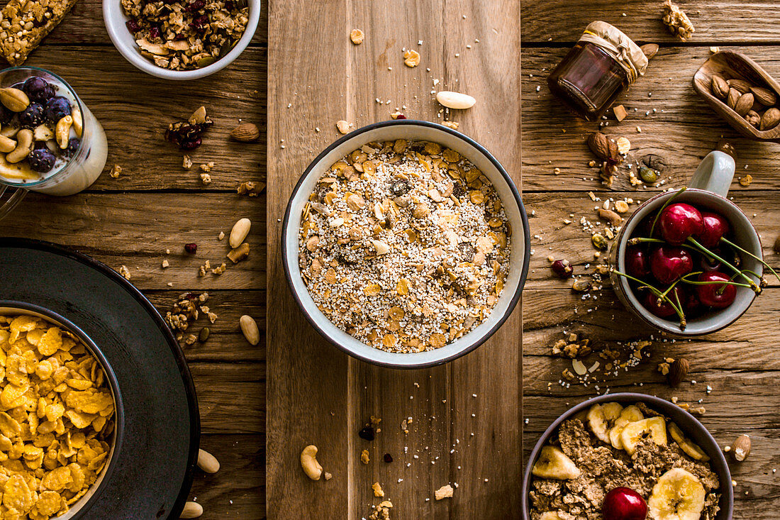 Muesli, cornflakes and fruit on a rustic wooden surface