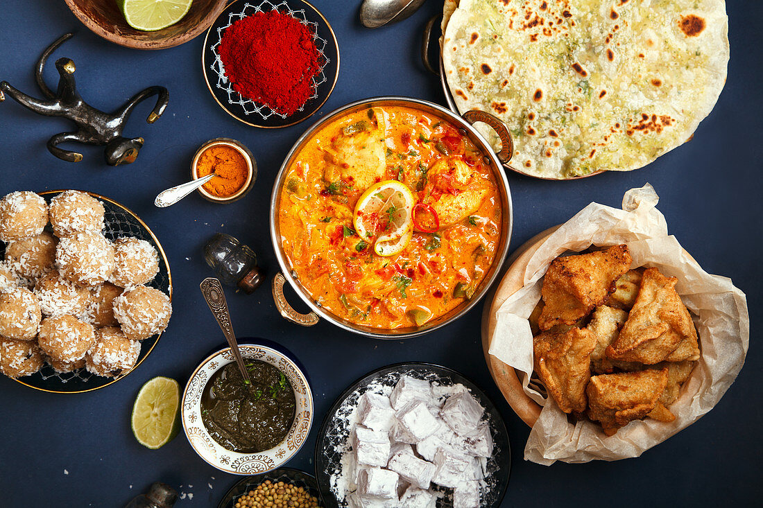 Indian cuisine on diwali holiday: Tikka masala, samosa, patties and sweets with mint chutney and spices
