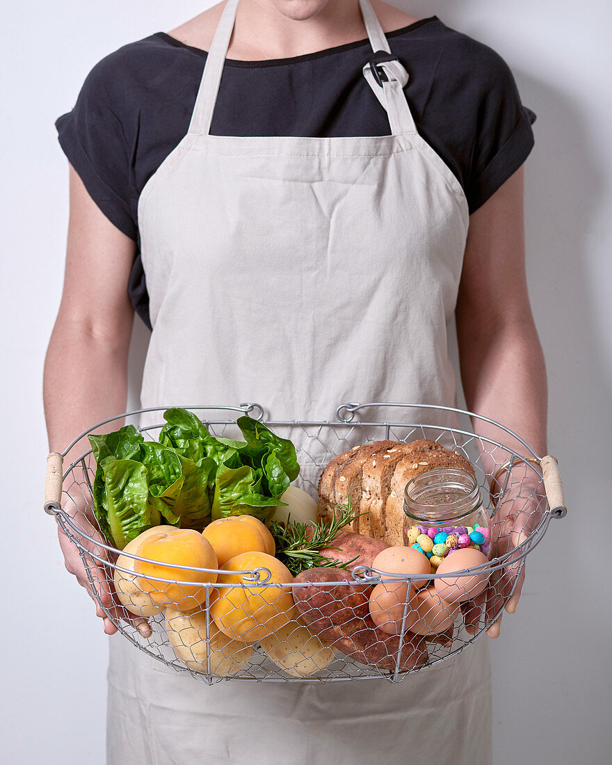 A woman holding a wire basket with bread, vegetables, apricots and other foods