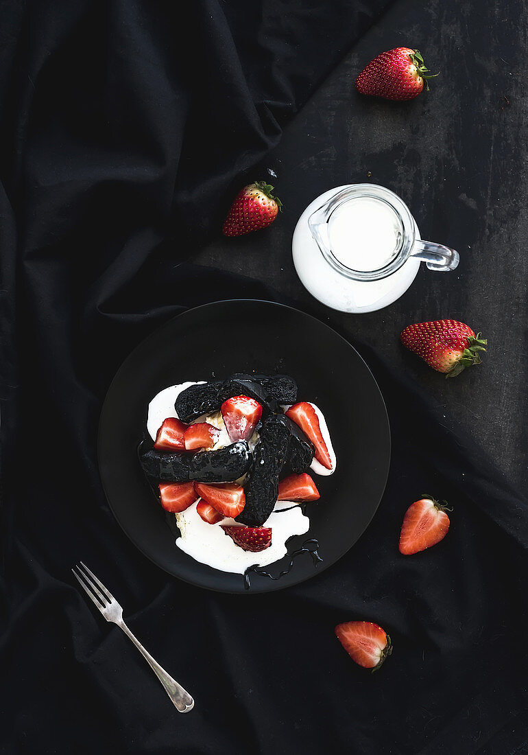 Black biscotti and strawberry dessert with sweet cream