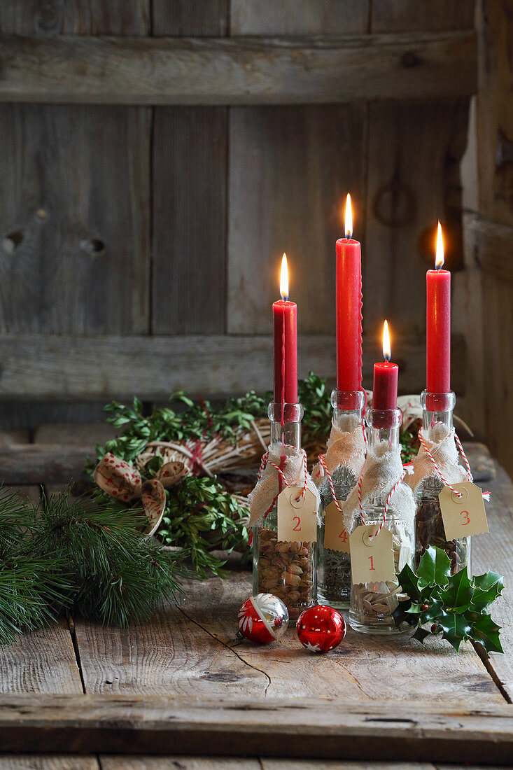 Bottles filled with nuts and herbs used as candlesticks on a rustic wooden background