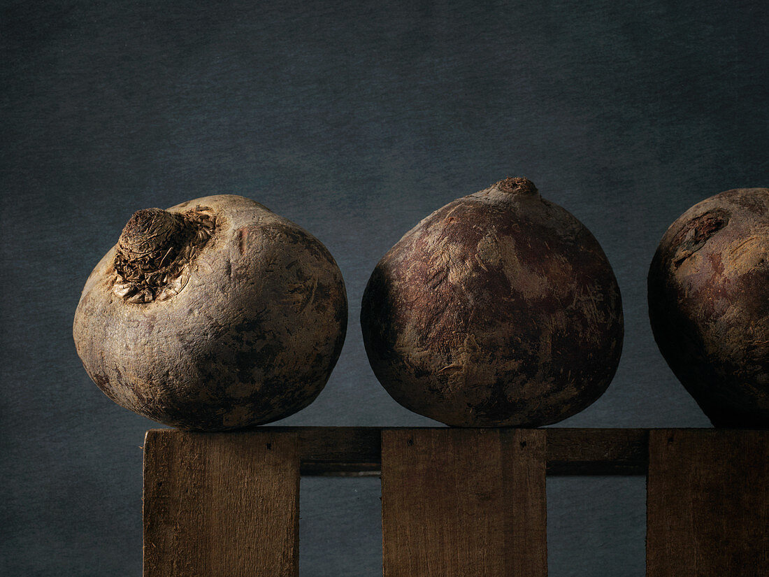 Three red beets on a wooden frame